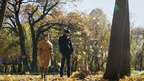 Het gelukkige familie spelen met de herfstbladeren in park Het mamma en de papa werpen omhoog weilanden in de lucht Het kleine ki stock footage