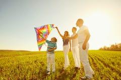 Het gelukkige familie spelen met een vlieger op aard in de lente, de zomer royalty-vrije stock fotografie