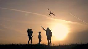 Het gelukkige familie spelen met een vlieger terwijl op weide, zonsondergang, in de zomerdag Grappige familietijd stock videobeelden