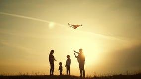 Het gelukkige familie spelen met een vlieger terwijl op weide, zonsondergang, in de zomerdag Grappige familietijd Het gelukkige m stock video