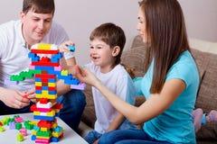 Het gelukkige familie spelen met kleurrijke blokken binnen thuis stock fotografie