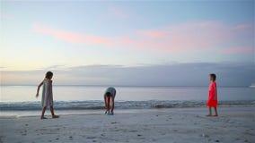 Het gelukkige familie spelen met vliegende schijf bij strand bij zonsondergang stock footage