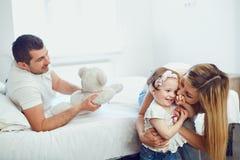 Het gelukkige familie spelen op het bed in de ruimte royalty-vrije stock afbeeldingen