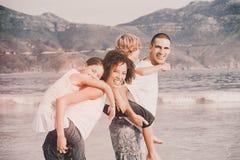 Het gelukkige familie spelen op het strand Stock Foto