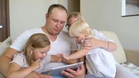 Het gelukkige familie spelen samen met laptop en digitale tablet thuis Vader, moeder en twee jonge geitjes die op bank zitten en stock video