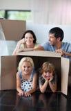 Het gelukkige familie spelen thuis met dozen royalty-vrije stock foto