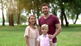 Het gelukkige familie stellen voor camera, concept het veilige leven, samenhorigheid en steun stock fotografie