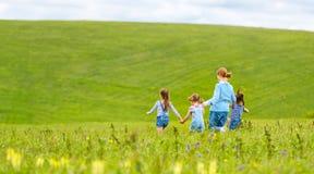 Het gelukkige familiemoeder en van de kinderendochter meisjes lachen en looppas Stock Foto