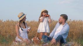 Het gelukkige familieportret, het jonge zoete broodje van vaderbeten van zijn dochter overhandigt en glimlacht aan vrouwenzitting stock footage