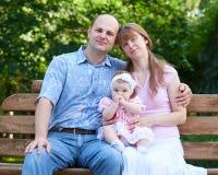 Het gelukkige familieportret met babymeisje op openlucht, zit op houten bank in stadspark, zomer, kind en ouder Royalty-vrije Stock Afbeeldingen