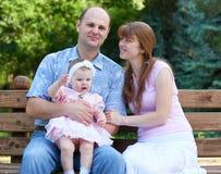 Het gelukkige familieportret met babymeisje op openlucht, zit op houten bank in stadspark, zomer, kind en ouder Stock Foto's
