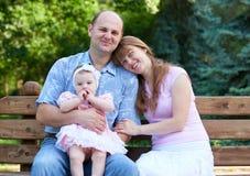 Het gelukkige familieportret met babymeisje op openlucht, zit op houten bank in stadspark, zomer, kind en ouder Stock Afbeelding