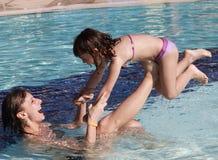 Het gelukkige familly spelen in de pool Stock Afbeeldingen