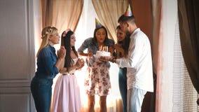 Het gelukkige feestvarken met vrienden maakt een wens en blaast uit de kaarsen op de cake stock video