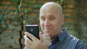 Het gelukkige Financiële Goede Nieuws van Zakenmansmile satisfied reading op Celtelefoon stock foto's