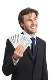 Het gelukkige geld van de zakenmanholding en zijdelings het kijken Stock Foto's