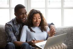 Het gelukkige gemengde goede nieuws van de raspaar verraste lezing online royalty-vrije stock foto