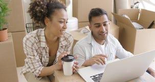 Het gelukkige gemengde raspaar bespreekt terwijl het gebruiken van laptop stock video