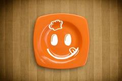 Het gelukkige gezicht van het smileybeeldverhaal op kleurrijke schotelplaat Stock Fotografie