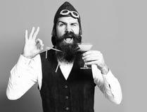 Het gelukkige glas van de gezichtsholding alcoholische drank in het uitstekende vest van het suèdeleer met hoed en glazen op rode stock fotografie