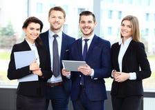 Het gelukkige glimlachen businessteam in bureau stock fotografie