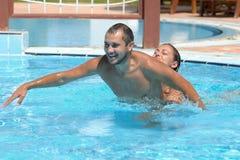 Het gelukkige glimlachen terwijl het ontspannen op de rand van een zwembad stock foto's