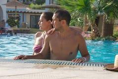 Het gelukkige glimlachen terwijl het ontspannen op de rand van een zwembad royalty-vrije stock afbeeldingen