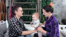 Het gelukkige het glimlachen twee jonge vrouw spelen met weinig baby die en liefde kussen voelen die goede tijd hebben stock videobeelden
