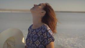 Het gelukkige glimlachende meisje stijgt haar op breed-brimmed strohoed en schudt haar hoofd stock videobeelden