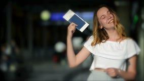 Het gelukkige glimlachende tienermeisje toont door vinger op haar paspoort en kaartje bij de luchthaven Vaag scorebord op stock footage