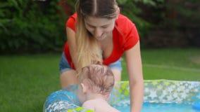 Het gelukkige het glimlachen babyjongen spelen met moeder in opblaasbaar zwembad bij binnenplaats stock footage
