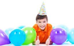 Het gelukkige het glimlachen boylying op de vloer met kleurrijke ballons Stock Foto