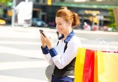 Het gelukkige het winkelen vrouw texting op een mobiele telefoon in Manhattan NYC Stock Foto