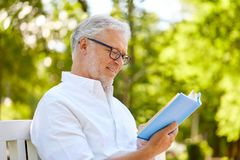 Het gelukkige hogere boek van de mensenlezing bij de zomerpark Royalty-vrije Stock Afbeelding