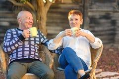 Het gelukkige hogere oude paar drinkt koffie door het park op zonnige dag stock afbeelding