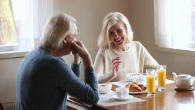 Het gelukkige hogere oudere paar spreken die hebbend gezond ochtendontbijt lachen stock footage