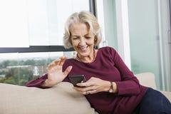 Het gelukkige hogere overseinen van de vrouwentekst door slimme telefoon op bank thuis Stock Afbeelding