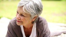Het gelukkige hogere vrouw ontspannen in park het denken stock videobeelden