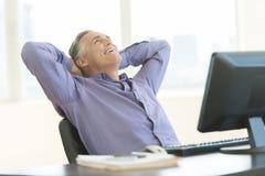 Het gelukkige Hoofd die van Zakenmanwith hands behind omhoog in Bureau kijken Stock Foto's