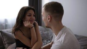 Het gelukkige het houden van paar ontspannen op bed thuis, jonge man wat betreft het glimlachen van mooie vrouwenbenen, die in de stock videobeelden