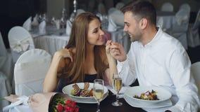 Het gelukkige houdende van paar houdt handen, spreekt en kust tijdens romantisch diner in restaurant hartelijk stock video