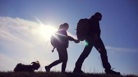 Het gelukkige huiselijke man en vrouwengroepswerk die gaat hand in hand silhouet van toeristen bovenop bergzonlicht lopen Paar stock videobeelden