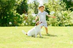 Het gelukkige jong geitje en huisdierenhond spelen met zeepbels bij binnenplaatsgazon royalty-vrije stock foto's