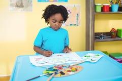 Het gelukkige jong geitje schilderen op een blad Royalty-vrije Stock Foto's