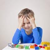 Het gelukkige jong geitje spelen met kleurrijke plastic bouwstuk speelgoed blokken bij de lijst Stock Foto's