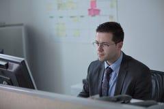 Het gelukkige jonge bedrijfsmensenwerk in modern bureau Knappe Zakenman In Office De echte econoom bussinesmen, niet een model royalty-vrije stock fotografie