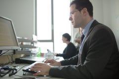 Het gelukkige jonge bedrijfsmensenwerk in modern bureau Knappe Zakenman In Office De echte econoom bussinesmen, niet een model stock afbeeldingen
