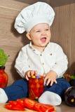 Het gelukkige jonge geitje de chef-kokkok kookt voedsel Stock Fotografie