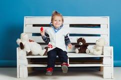 Het gelukkige jonge geitje met stuk speelgoed huisdieren zit op houten bank royalty-vrije stock afbeeldingen