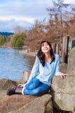 Het gelukkige jonge gezicht van het tienermeisje draaide om, glimlachend, terwijl het zitten in openlucht op rotsen langs meerkus Royalty-vrije Stock Fotografie
